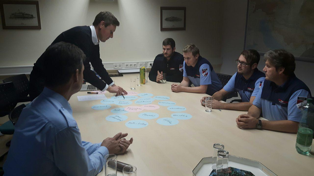 Workshopteilnehmer sammeln sich um einen Tisch mit Post Its